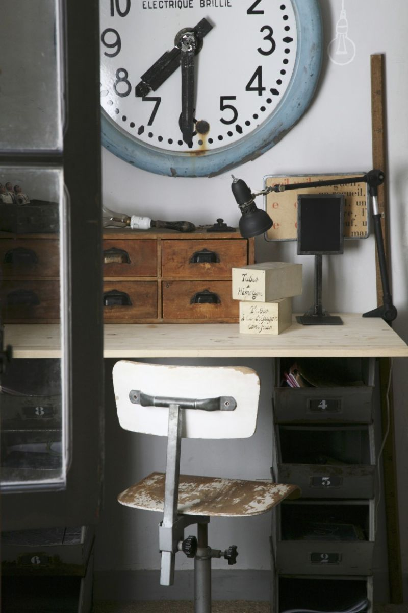 Old station clock above vintage desk with wooden organiser boxes and wooden swivel chair with peeling paint