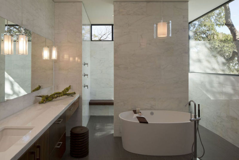 stylish-marble-bathroom-for-private-heaven-aura-with-bath-space-using-round-white-bathtub-pendant-lamp-above-also-near-mirror-as-washingstand-lamps
