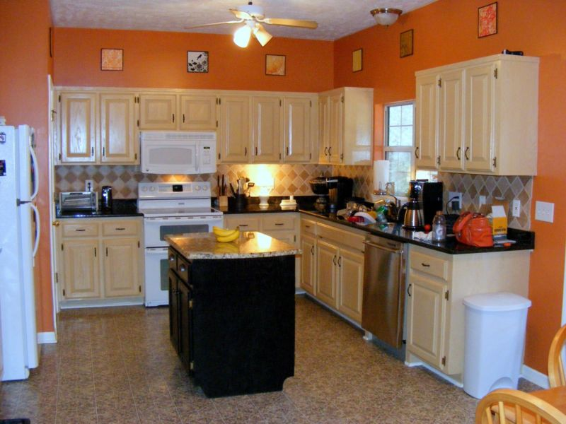 orange-kitchen-wall-paint-with-wood-kitchen-set-and-table-in-the-middle