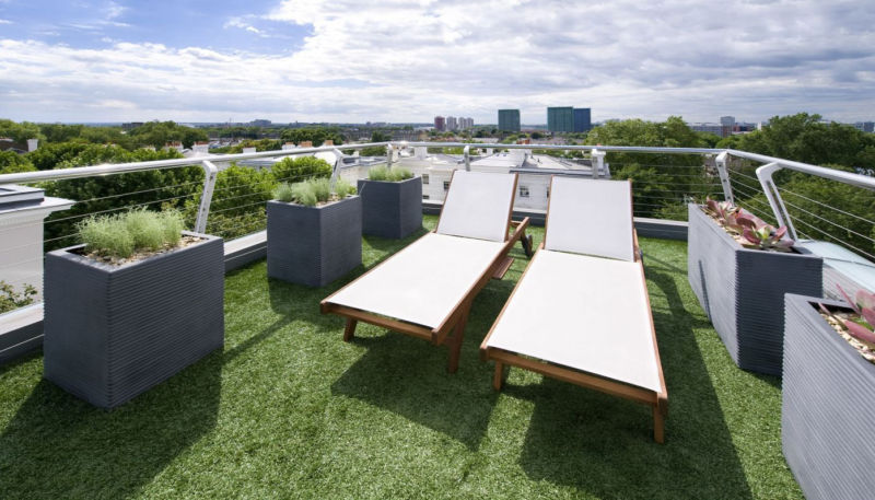 two-lounge-chairs-in-roof-top-balcony-with-green-grass-floor