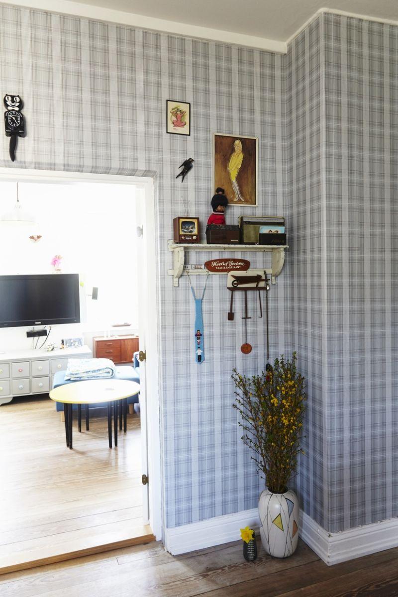 Diele mit karierter Tapete, Bodenvase unter Wandboard, neben offener Tür zu Wohnzimmer