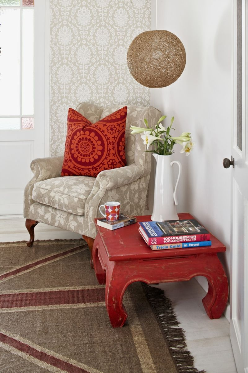 Reading corner; opium table and pale armchair with patterned scatter cushions against wallpapered wall